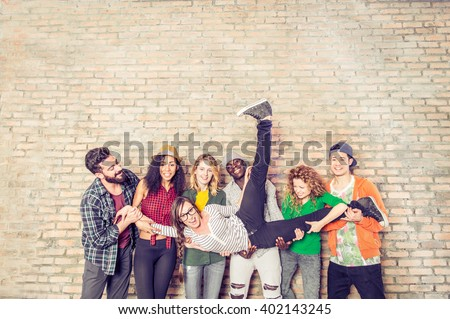Group portrait of multi-ethnic boys and girls with colorful fashionable clothes holding friend and posing on a brick wall - Urban style people having fun - Concepts about youth  and togetherness - stock photo