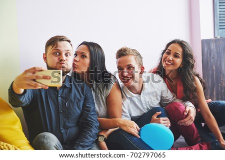 Group portrait of multi-ethnic boys and girls with colorful fashionable clothes holding friend and posing on a brick wall, Urban style people having fun, Concepts about youth and lifestyle.