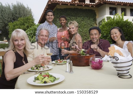 Group portrait of multiethnic friends enjoying dinner party in garden - stock photo