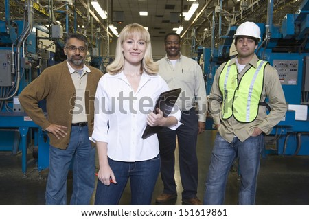 Group portrait of multiethnic operators standing in the factory