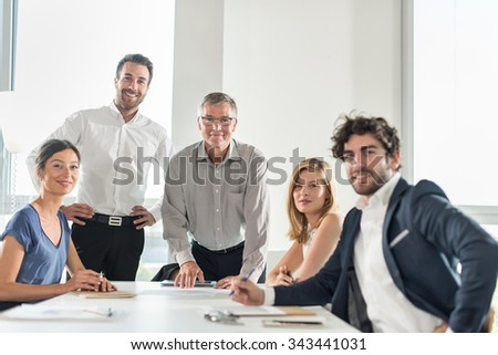 Group portrait of office coworkers with their grey hair senior boss with glasses. They are looking at camera around a white table in a luminous office.There are two women and three men, real people - stock photo