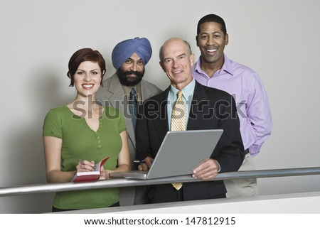 Group portrait of smiling multiethnic businesspeople with laptop - stock photo