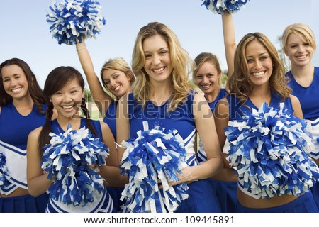 Group portrait of young cheerleaders holding pom-poms on field - stock photo