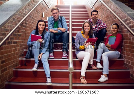 Group portrait of young college students sitting on stairs in the college - stock photo