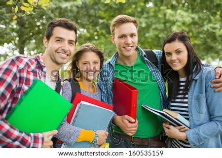 Group portrait of young college students with bags and books standing in the park - stock photo