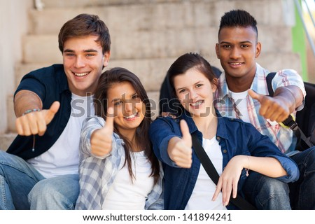 group smiling high school students giving thumbs up - stock photo