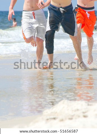 group splashing on the beach - stock photo