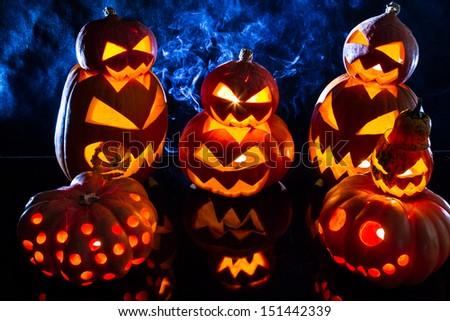Group strange halloween pumpkins on black background with smoke - stock photo
