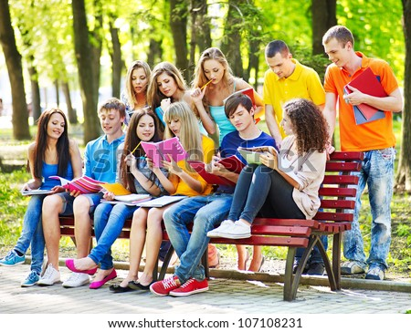 Group student with book on bench outdoor.