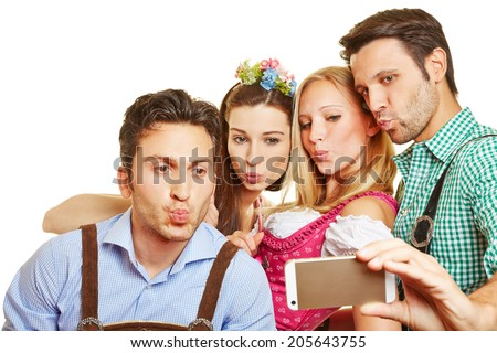 Group taking selfie with duckface at Oktoberfest in Bavaria - stock photo