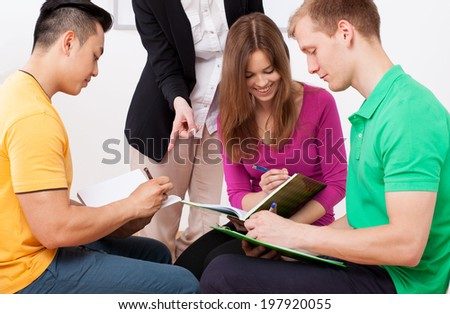 Group task at the lesson and teacher - stock photo