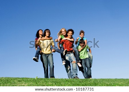 group teenagers in piggy back race (Some slight motion blur) - stock photo