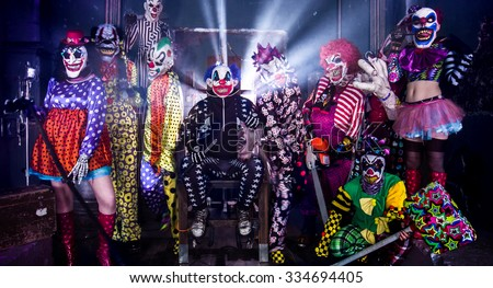 Group terrifying clowns. King clown in the electric chair. Halloween party. - stock photo