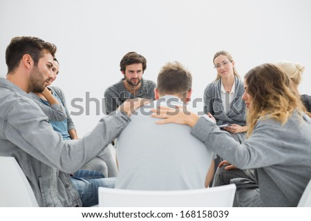 Group therapy in session sitting in a circle with therapist - stock photo