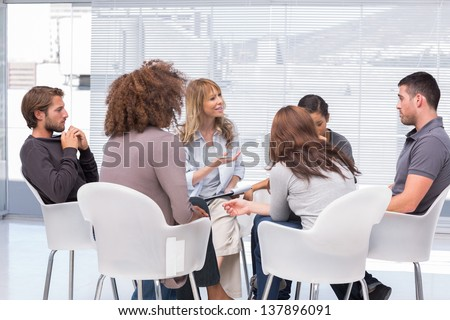 Group therapy session sitting in a circle - stock photo