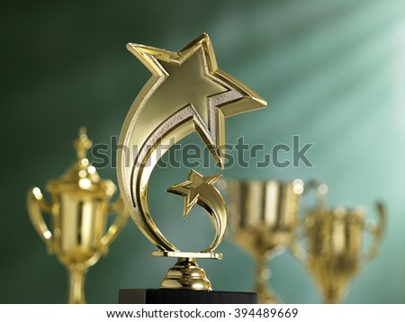 group trophies in front of blackboard with light ray effect - stock photo