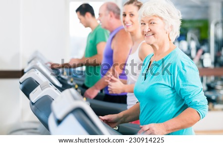 Group with senior and young men and women people on treadmill in fitness gym running for sport - stock photo