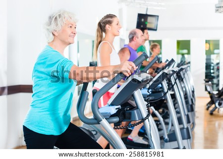 Group with young and Senior women and men on elliptical trainer exercising in gym - stock photo