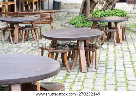 Group wooden tables in a traditional Bulgarian style on a street cafe, Tryavna, Bulgaria