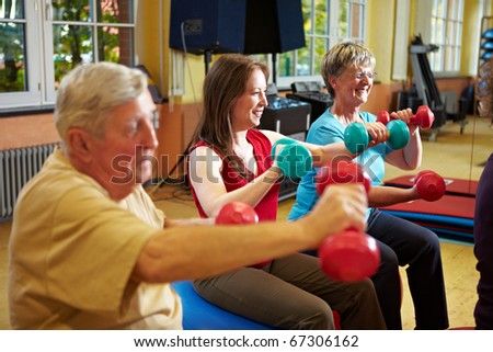 Group working out with dumbbells in gym - stock photo