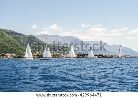"Group yachts to the shore. Tivat, Montenegro - 26 April, 2016. Regatta ""Russian stream"" in God-Katorskaya bay of the Adriatic Sea off the coast of Montenegro. - stock photo"