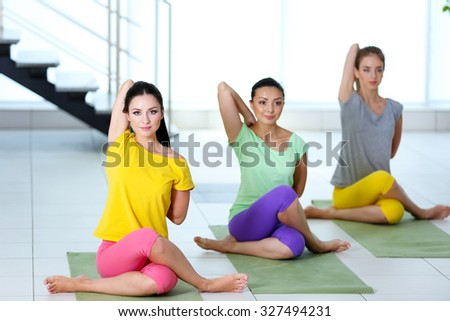 Group yoga exercise for young women in a class - stock photo