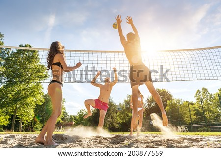 Group young  Friends Playing Volleyball On Beach - stock photo