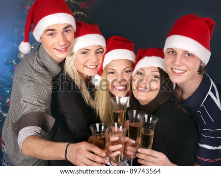 Group young people in Santa hat drink champagne at nightclub. - stock photo