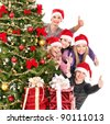 Group young people in Santa hat showing thumb up by Christmas tree.. - stock photo