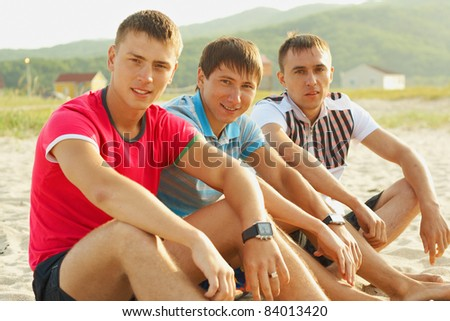 Group young people resting on the sand