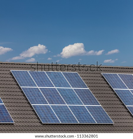 Grouped solar panels on a roof of newly build European houses - stock photo