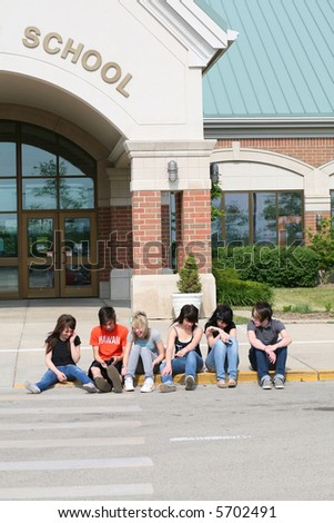 groups of attractive teens outside school entrance - stock photo