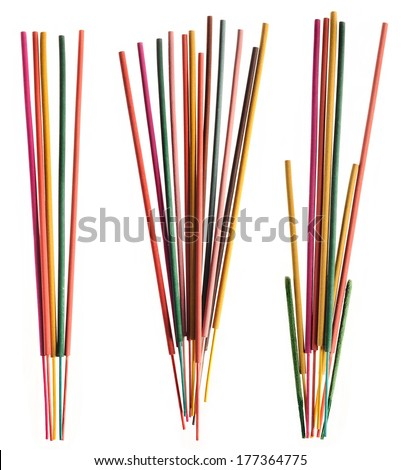 Groups of colorful incense sticks on white background.