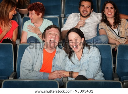 Groups of friends in the audience laugh and smile - stock photo