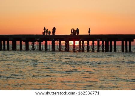 Groups of people on the old pier admire the beautiful sunset over the Black Sea coast in Crimea, Ukraine - stock photo