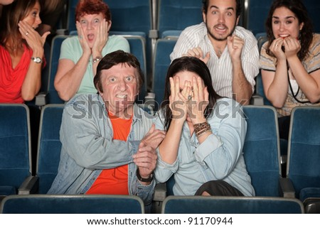 Groups of scared people in movie theater - stock photo