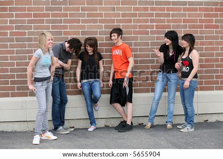 groups of trendy teens laughing outside of school - stock photo