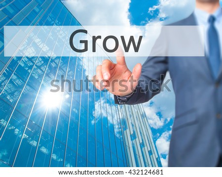 Grow - Businessman hand pressing button on touch screen interface. Business, technology, internet concept. Stock Photo