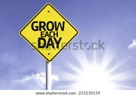 Grow Each Day road sign with sun background  - stock photo