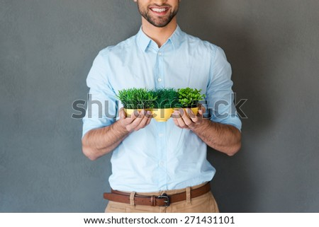 Grow up your business. Cropped picture of cheerful young man in shirt holding flower pot and smiling at camera while standing against grey background  - stock photo