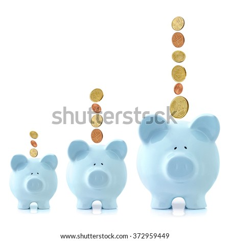 Growing piggy banks with Euro coins falling.  Investment growth concept. - stock photo