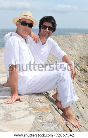 Grownup father and son sitting on a harbor wall - stock photo