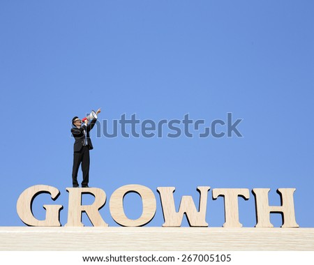 Growth business concept - business man stand on Growth text word and using megaphone shouting with blue sky background - stock photo