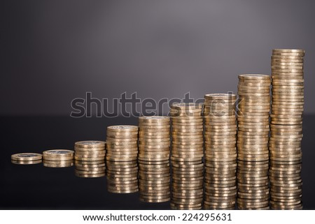 Growth chart made from coins over black background - stock photo