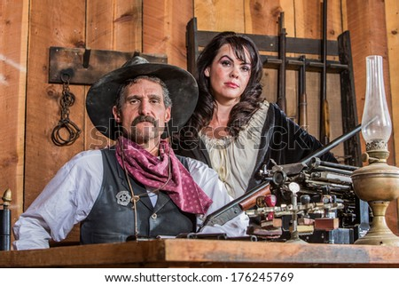 Gruff Cowboy Poses With A Rifle And Stern Saloon Girl - stock photo