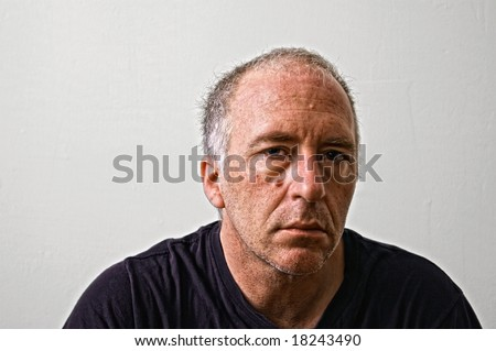 gruff looking man looking tired gazing at viewer - stock photo