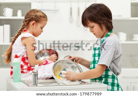 Grumpy kids doing home chores on parents order - washing dishes - stock photo