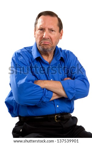 Grumpy moody senior man sits with his arms crossed and an unhappy expression on his face. - stock photo