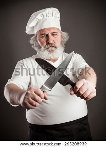 Grumpy old chef with two knives against dark background - stock photo