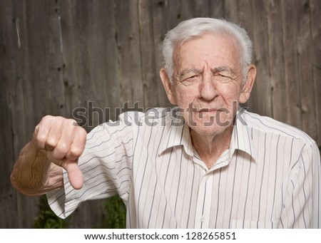 Grumpy old man giving thumbs down - stock photo